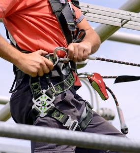 A construction worker ties a safety harness to climb an electricity pylon