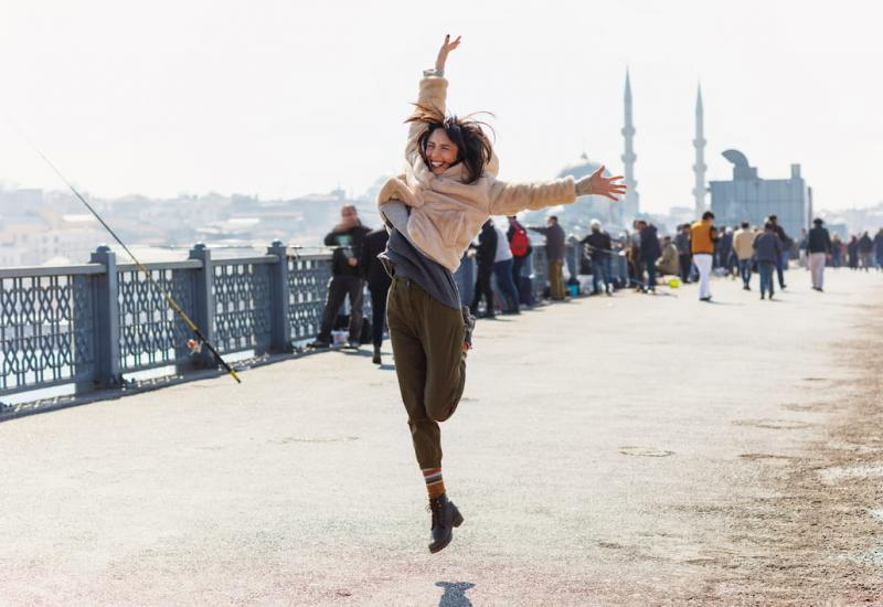 A woman jumps for joy on Galata bridge, Istanbul, Turkey