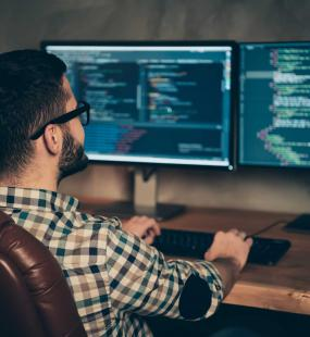 A bearded man in glasses sits in a leather chair at a wooden desk, coding across two monitors