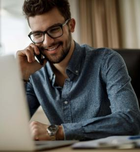 A smiling young businessman sits at his computer and speaks on the phone