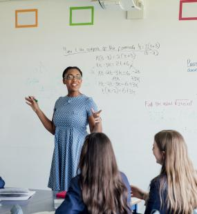 Women standing at a whiteboard educating a class of kids
