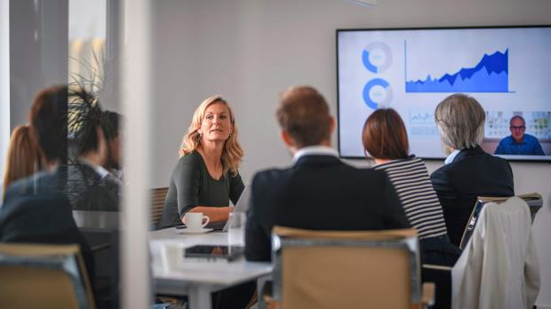 blonde business woman speaks to a colleague during a board meeting, where everyone around the table sits looking at a presentation on a large screen