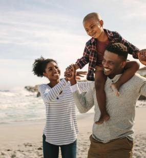 A young family of three walk along the beach. The father carries his happy son on his shoulders and holds his hands. The mother walks next to them and reaches towards her son. All three of them have big smiles