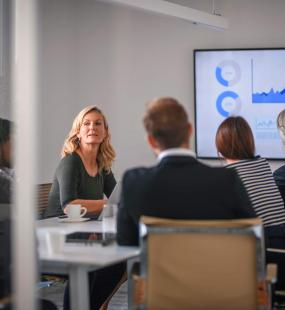 A blonde businesswoman listens to her colleague during a video conference call in a busy boardroom
