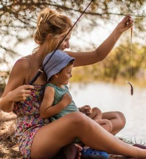 A woman and her young son are fishing by the side of a sunny lake. She holds up a small fish on the line as he smiles happily