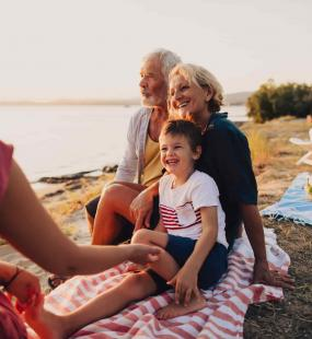 An attractive older couple sits on a picnic blanket by the sea with their daughter and grandson. They are all smiling, and the man looks out at the sea
