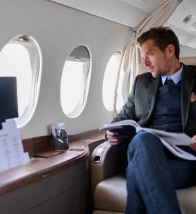 A suave gentleman in a tailored suit looks out of the window of his private jet