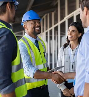 A team of four engineers and architects speak on a construction site. Two wear high visibility jackets and safety hats. One smiling man in a high vis shakes the hand of a man in a blue shirt