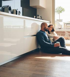 A couple sit on the floor of their luxury modern kitchen