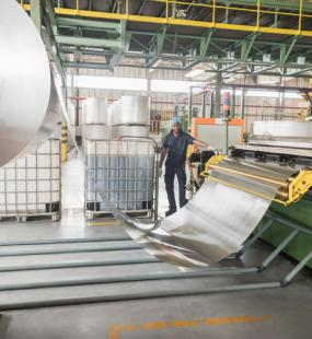 A male factory worker stands in a warehouse by a large roll of aluminium