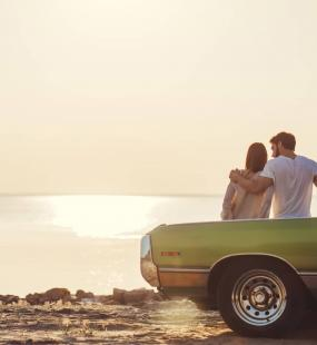 A young couple lean on the bonnet of a vintage green car and watch the sun set over the sea