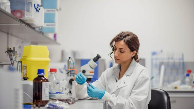 A female researcher or biochemist, sitting in a lab wearing a lab coat and blue plastic gloves, analyses a specimen in a test tube
