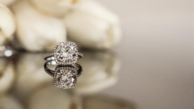 A diamond ring sitting on a reflecting surface in front of some white roses