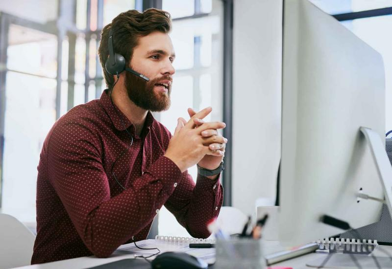A friendly young professional with a beard talks into a headset while sitting at a desk