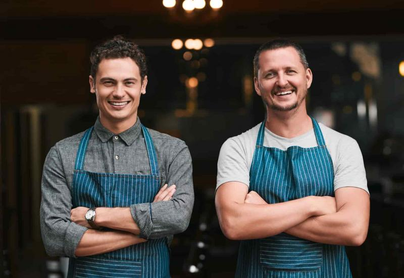 Two business owners stand in front of the open door to their restaurant. They are wearing aprons and stand smiling with their arms crossed